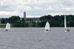 Sport che navigano nei lotti di piccole barche bianche sul lago Fotografie Stock