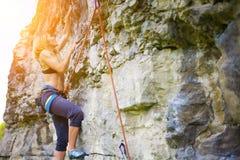 Sport climbing outdoors. Girl climbs down a dangerous wall, sport climbing outdoors Stock Images