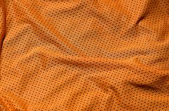Sport clothing fabric texture background. Top view of orange polyester nylon cloth textile surface. Colored basketball shirt with. Free space for text royalty free stock photo