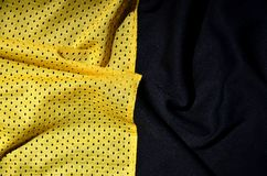 Sport clothing fabric texture background. Top view of yellow polyester nylon cloth textile surface. Colored basketball shirt with. Free space for text royalty free stock image