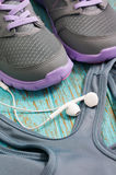 Sport clothing and shoes with earphones. Sport clothing, running shoes and earphones on wood background Stock Photography