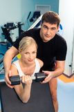 In the sport club. Blonde woman lifting weight with man assisting her in the sport club Royalty Free Stock Photo