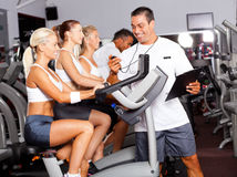 Sport coach. Timing cyclist on gym bike Stock Images