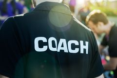 Sport coach in black shirt with white Coach text on the back sta. Nding outdoor at a school field, with morning lens flare, good for coaching or sport concept stock photography