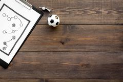 Sport coach concept. Pad with tactic plan of the match near whistle and football ball on wooden background top view copy. Sport coach concept. Pad with tactic royalty free stock photography