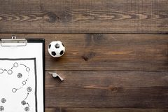 Sport coach concept. Pad with tactic plan of the match near whistle and football ball on wooden background top view copy. Sport coach concept. Pad with tactic stock image