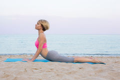 Sport cobra pose. Stretching of abdominal muscles on the beach. cobra pose  Young beautiful girl on a rug on the sandy beach. Rays of the setting sun Stock Images