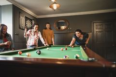Sport Comes in All Forms. Small group of female friends playing a game of pool in a games room in a house stock image