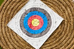 Shooting target and bullseye with many bullet holes. Sport competitions equipment concept. Shooting paper target and bullseye in haystack with many bullet holes Stock Image