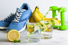 Sport composition with sports equipment glass water with lemon m Royalty Free Stock Image