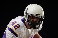 Close up portrait of American football sportsman player in action on black background. Sport concept. royalty free stock photography