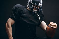 American football player in black sportwear with a ball on black background stock image