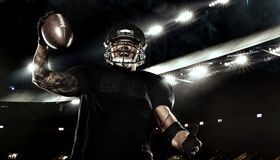 Sport concept. American football sportsman player holding ball on stadium. American Football player on stadium with smoke and lights Royalty Free Stock Images