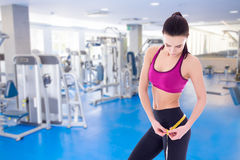 Sport concept - beautiful slim sporty woman with measure tape in Stock Image