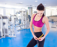 Sport concept - beautiful slim sporty woman measuring her waistl Royalty Free Stock Photography