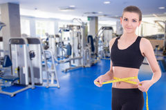 Sport concept - beautiful slim sporty woman measuring her waistl. Ine with measure tape in modern gym Stock Image
