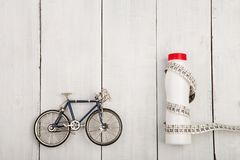 Sport concept -  bicycle model, bottle of water and centimeter t Stock Image