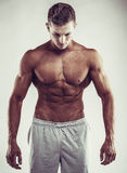 Sport concept. Close up image of muscular caucasian male in sports clothing over grey background Stock Photos