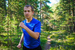 Sport concept - handsome man jogging in forest Stock Photos