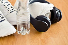 Sport concept. headphones, shoes and water in bottle Royalty Free Stock Photography