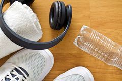Sport concept. headphones, shoes and water in bottle Royalty Free Stock Images