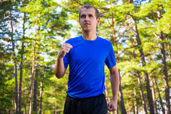 Sport concept - male runner jogging in forest Stock Photo