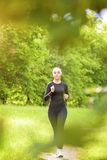 Sport Concept: Positive Caucasian Fit Woman Having Her Regular Jogging Royalty Free Stock Images