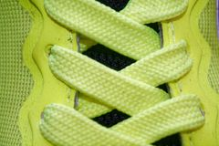 Sport concept, shoe close up, wellness concept, yellow lace on blue sneakers close up. Detail of yellow shoe on running shoes. Royalty Free Stock Photos