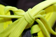Sport concept, shoe close up, wellness concept, yellow lace on blue sneakers close up. Detail of yellow shoe on running shoes. Royalty Free Stock Photography