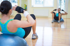 Sport concept - young sporty woman doing exercises on bosu ball Royalty Free Stock Images