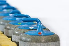 Sport Concepts. Closeup of Curling Blue Handle Stones on Ice. Royalty Free Stock Image