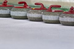 Sport Concepts. Closeup of Curling Red Handle Stones on Ice. Royalty Free Stock Image