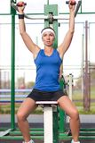 Portrait of concentrated caucasian female training her arm muscles on a trainer outdoors. Sport Concepts. Portrait of Concentrated Caucasian Female Training Her royalty free stock images