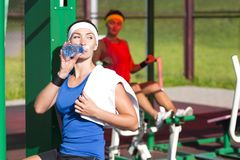 Sport concepts. Two positive caucasian female athlete in good fit. Having Training Outdoors. One is Drinking Water and Relaxing with Towel. Horizontal Image Stock Images