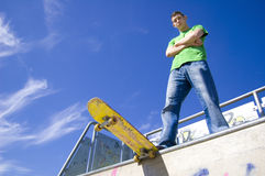 Sport conceptual image. Teenage skateboarder standing on the ramp with skateboard Stock Photography
