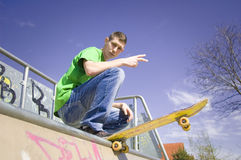 Sport conceptual image. Teenage skateboarder standing on the ramp with skateboard and shows a youth gesture Royalty Free Stock Images