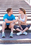 Sport connecting people. Side view of beautiful young couple in sports clothing sitting on stairs face to face and smiling royalty free stock images
