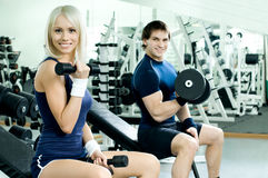 Sport couple. Happy cutie athletic girl and guy,  exercise with dumbbells and smile, in  sport-hall Royalty Free Stock Photos