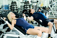 Sport couple. Happy cutie athletic girl and guy,  lie exercise with dumbbells and smile, in  sport-hall Stock Images