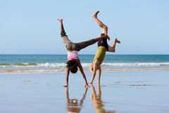 Sport couple doing gymnastics on the beach. Young sport couple - Caucasian man and African-American woman – doing gymnastics on the beach Royalty Free Stock Photo
