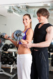 Sport - couple is exercising with barbell in gym Stock Image