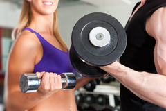 Sport - couple is exercising with barbell in gym Stock Photo
