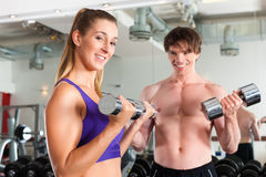 Sport - couple is exercising with barbell in gym Royalty Free Stock Image