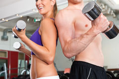 Sport - couple is exercising with barbell in gym Stock Photography