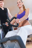 Sport - couple is exercising on machines in gym Stock Photos