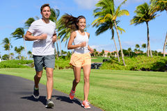 Sport couple exercising running outside on street Stock Photos