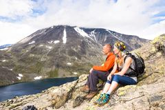Sport couple hiking on Besseggen. Hikers enjoy beautiful lake and good weather in Norway. Sport couple hiking on Besseggen. Hikers enjoy beautiful lake and good Stock Images