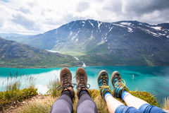 Sport couple hiking on Besseggen. Hikers enjoy beautiful lake and good weather in Norway. Royalty Free Stock Image