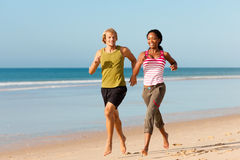 Sport couple jogging on the beach. Young sport couple - Caucasian man and African-American woman - jogging on the beach stock photography