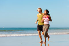 Sport couple jogging on the beach. Young sport couple - Caucasian man and African-American woman - jogging on the beach Royalty Free Stock Photos